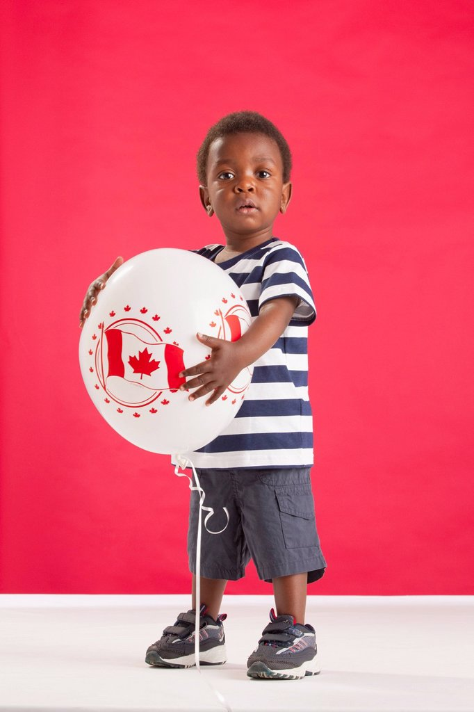 A Young Boy Holding A Balloon With A Picture Of The Canada Flag : Stock Photo