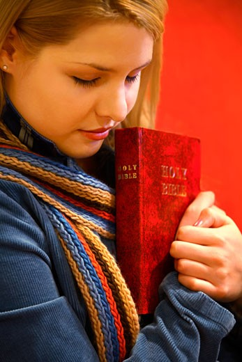 Stock Photo: 1889R-6179 Teen holds Bible and prays