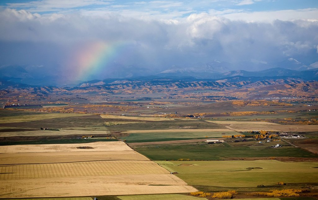 Stock Photo: 1889R-61813 a rainbow over the mountains with storm clouds and the colors of autumn in fields, alberta, canada