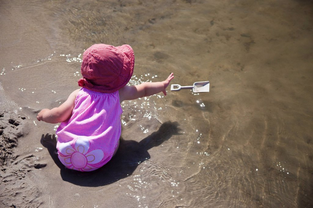 a young girl sits in the wet sand at the water´s edge reaching for her floating shovel, county of st. paul, alberta, canada : Stock Photo