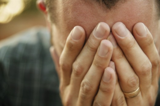 Man with hands over his face : Stock Photo