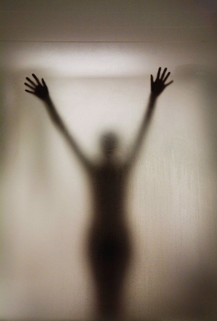 silhouette of a nude woman behind the glass door of a shower stall : Stock Photo