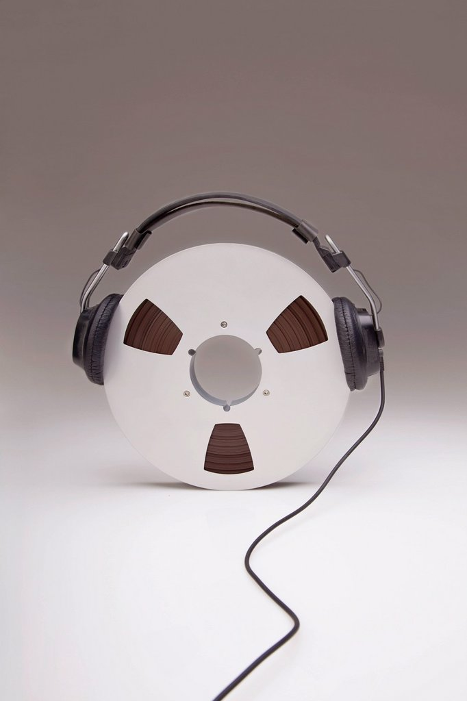 Stock Photo: 1889R-64671 headphones on a reel of recording tape