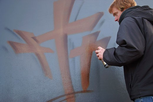 Man spray painting crosses : Stock Photo