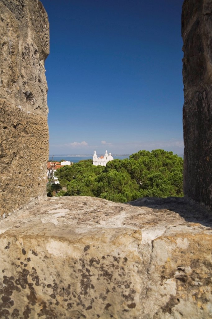 view of a cathedral through a rampart wall at st_jorge castle, lisbon, portugal : Stock Photo