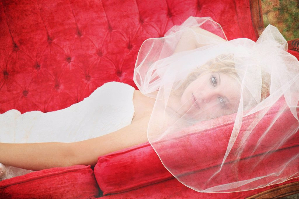 Stock Photo: 1889R-67296 a bride´s face behind her veil as she lays on a red couch