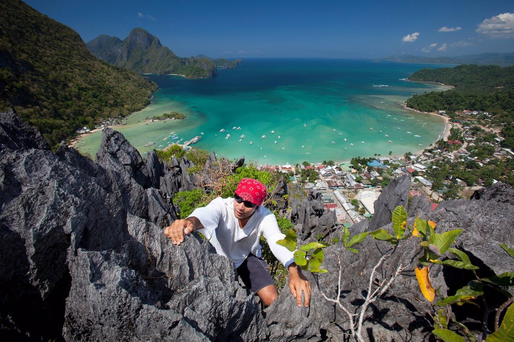 a man rock climbs on top of sharp limestone spires overlooking the village of el nido, el nido, bacuit archipelago, palawan, philippines : Stock Photo