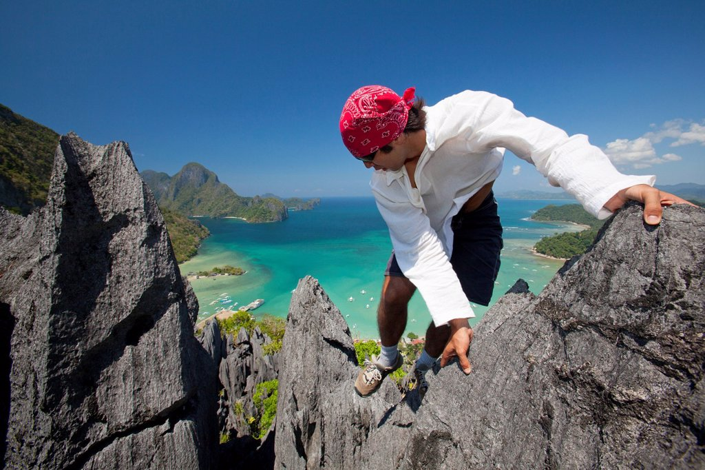 Stock Photo: 1889R-67627 a man rock climbs on top of sharp limestone spires overlooking the village of el nido, el nido, bacuit archipelago, palawan, philippines