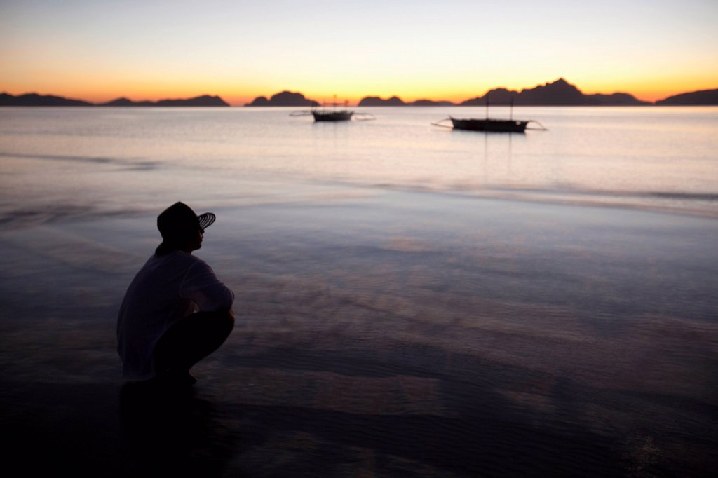 a man on a beach at sunset, corong_corong, palawan, philippines : Stock Photo