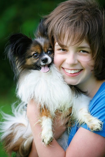 a young girl hugs her papillon dog, victoria, vancouver island, british columbia, canada : Stock Photo