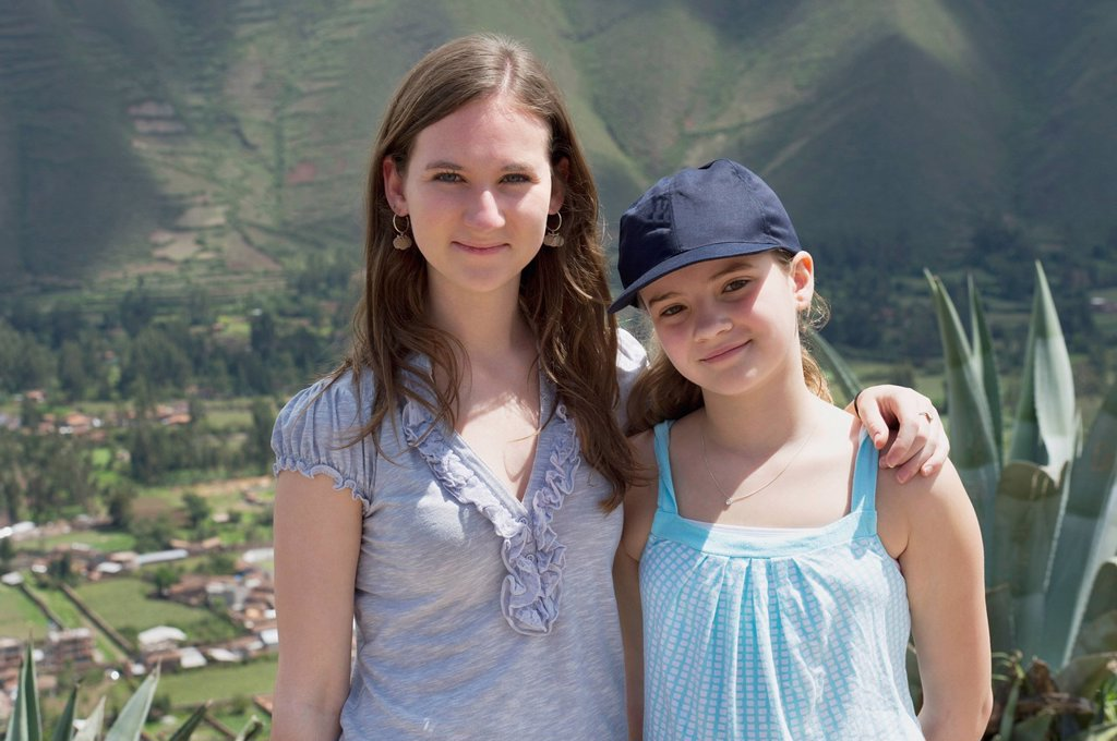two sisters standing together with sacred valley below them, sacred valley peru : Stock Photo