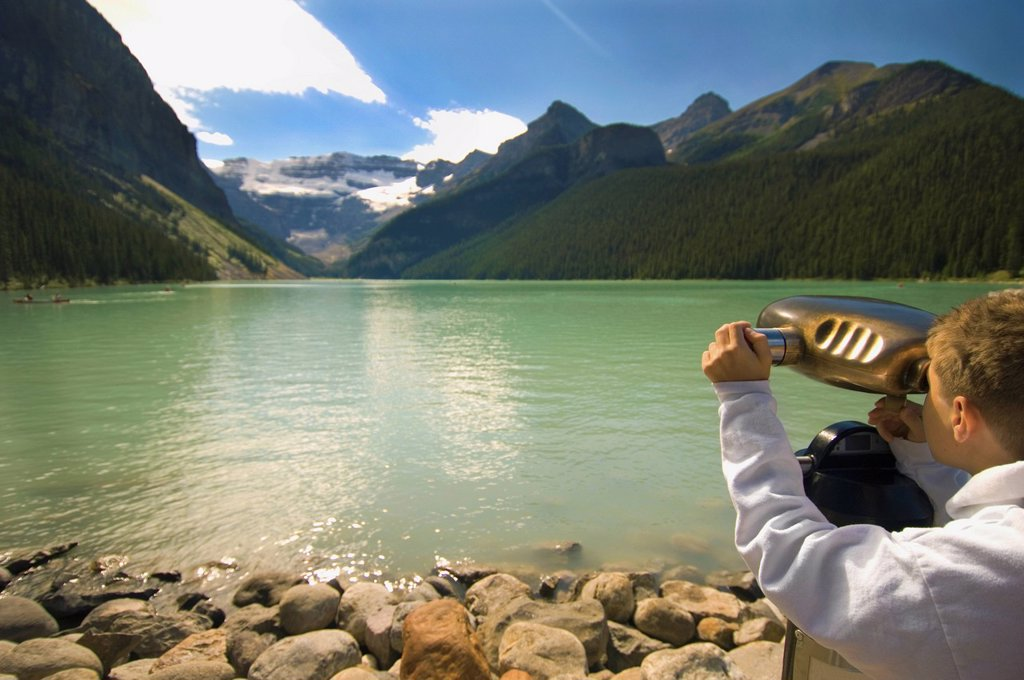 Stock Photo: 1889R-68373 a boy looking through binoculars at a view of the mountains over lake louise, alberta canada