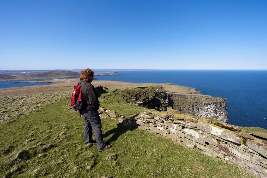 a woman stands looking out over the ocean, noss scotland : Stock Photo