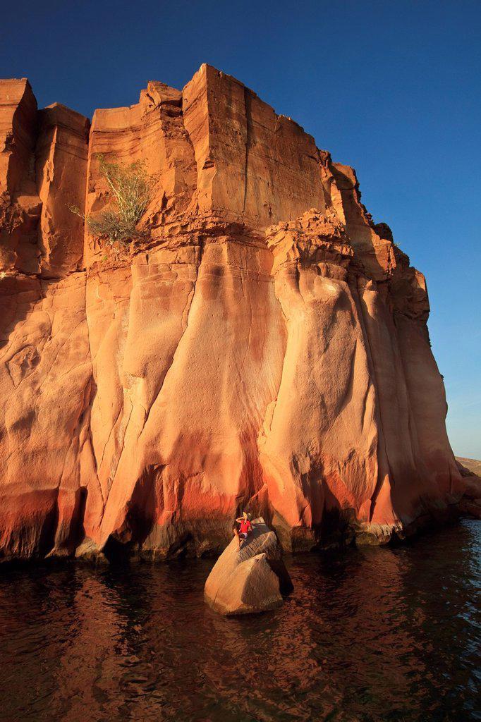 a person lays on a rock in the water on the shoreline of espiritu santo island near la paz, baja california mexico : Stock Photo
