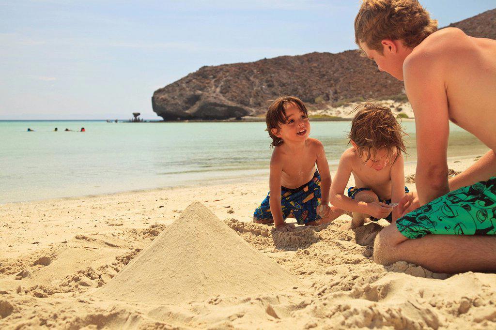 Stock Photo: 1889R-68865 three boys play in the sand at the water´s edge at los islotes national marine park espiritu santo island, la paz baja california mexico