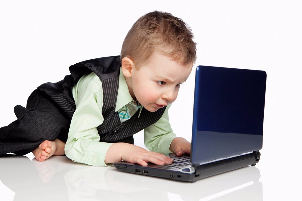 Stock Photo: 1889R-68901 a young boy dressed in a suit using a laptop computer, edmonton alberta canada