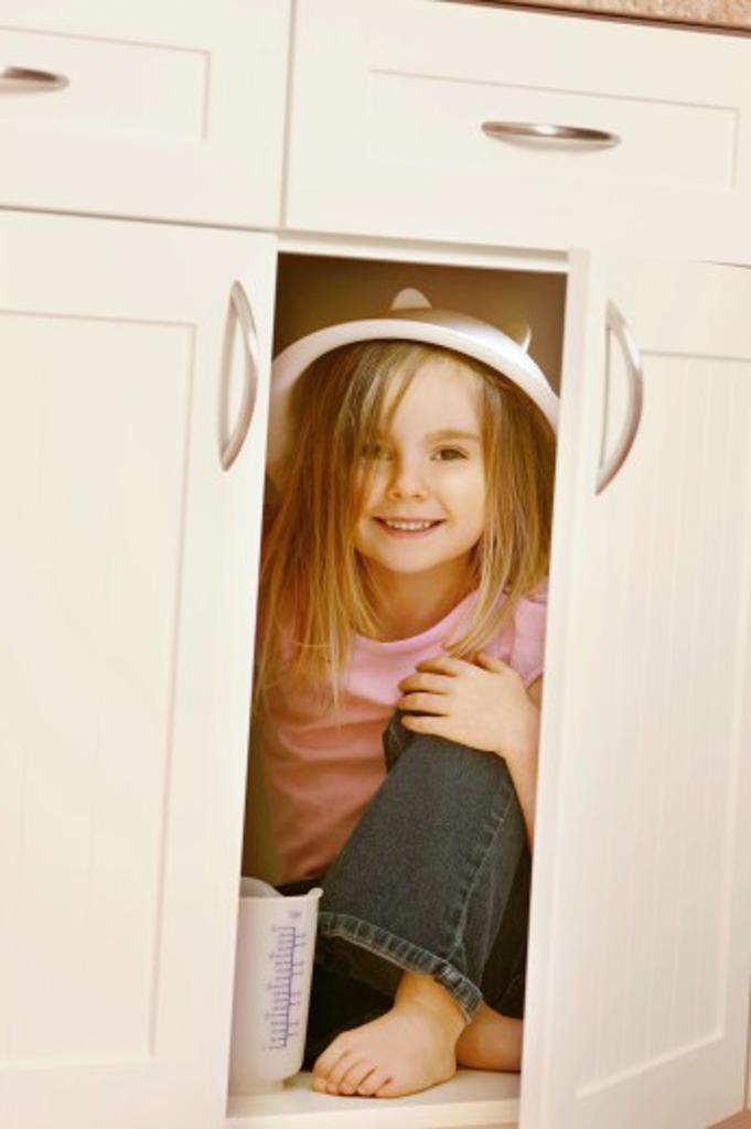 Child hides in kitchen cupboard : Stock Photo