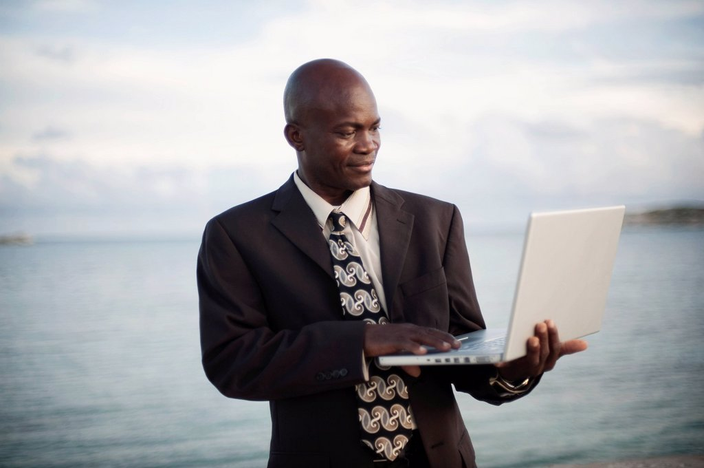 Stock Photo: 1889R-69159 a businessman using a laptop computer by the water´s edge, south caicos turks and caicos islands