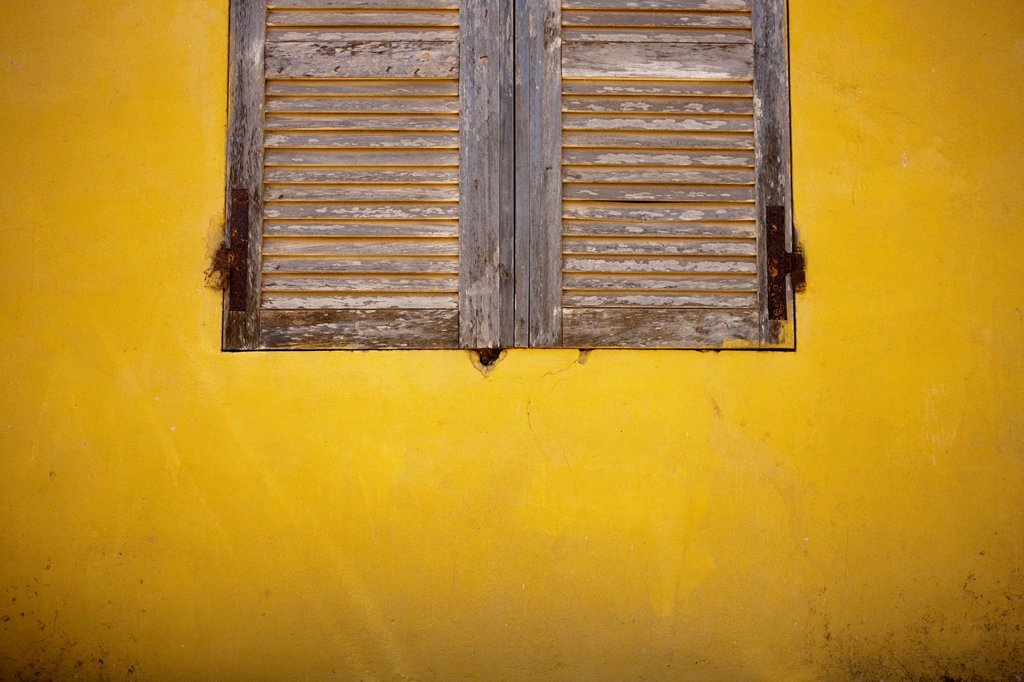 wooden shutters on a yellow wall, dakar senegal : Stock Photo