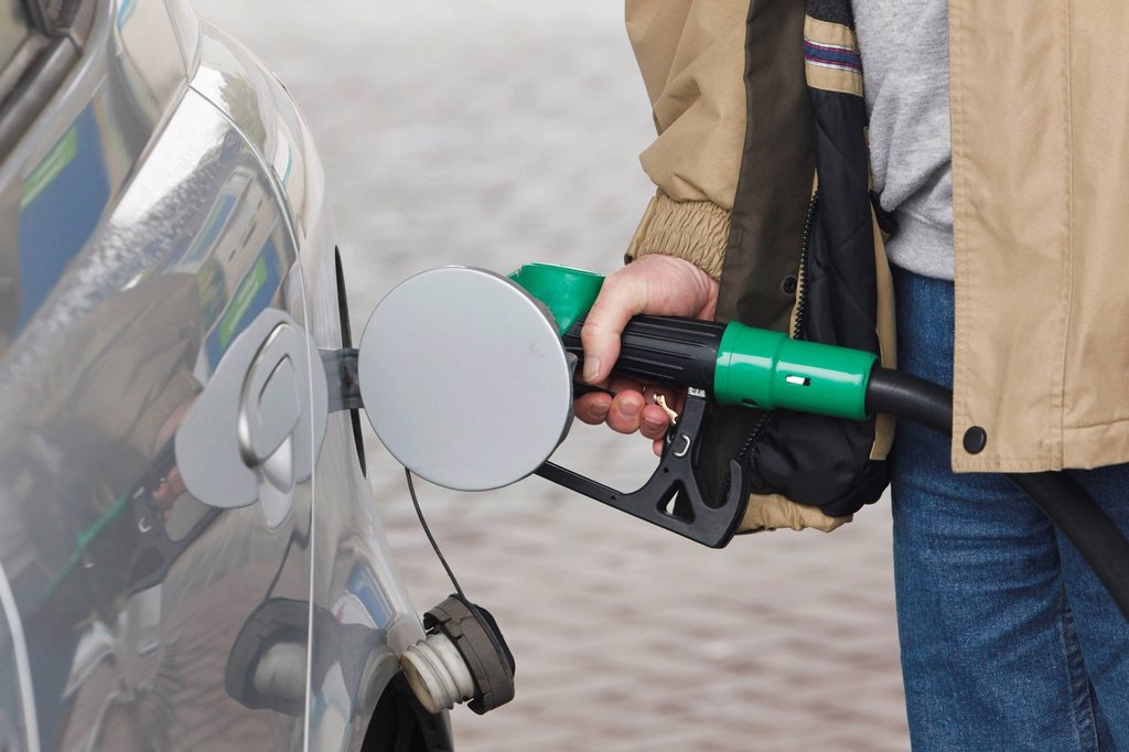 man pumping petrol into car, dunmanway county cork ireland : Stock Photo
