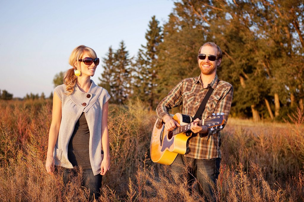 Stock Photo: 1889R-70151 a couple standing in a field with a guitar, edmonton alberta canada