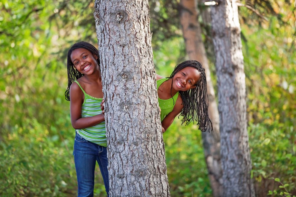 Stock Photo: 1889R-70309 sisters hiding behind a tree in a park, edmonton alberta canada