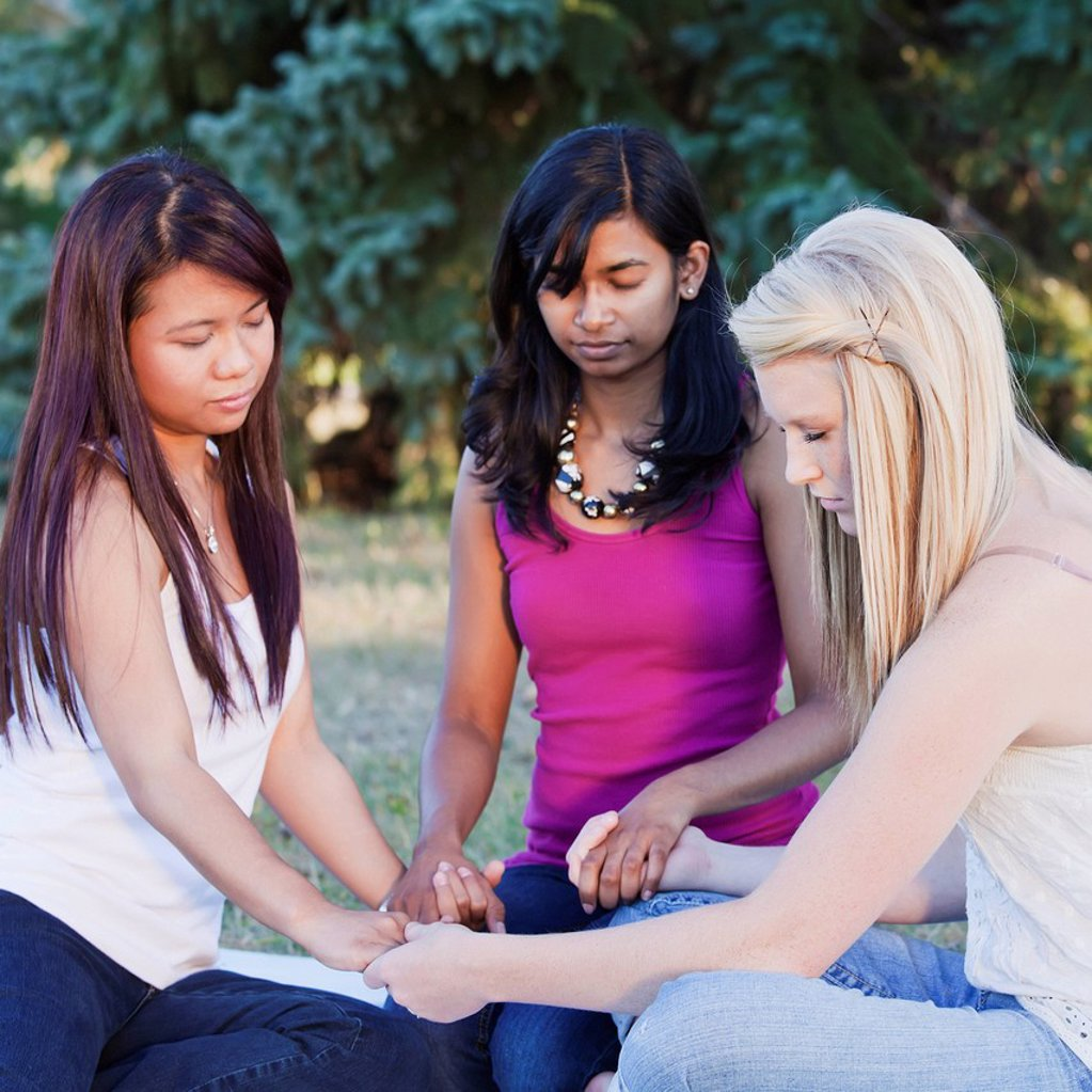 Stock Photo: 1889R-70397 friends holding hands and praying together, edmonton alberta canada