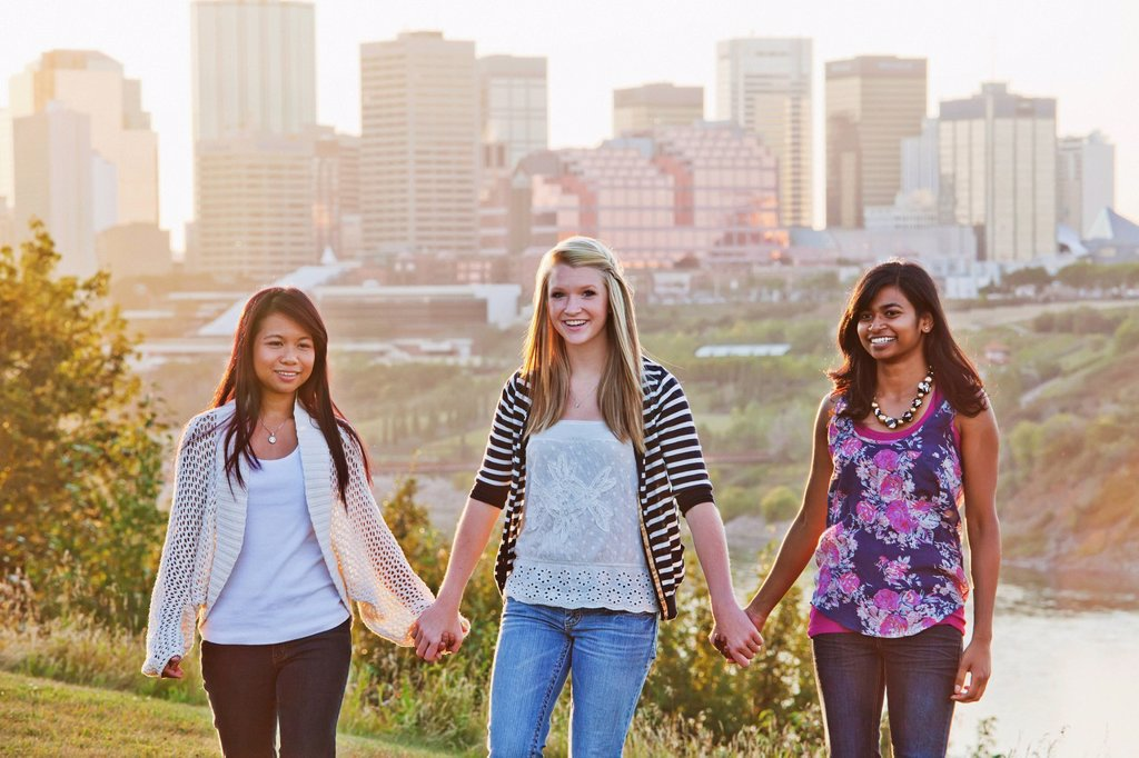Stock Photo: 1889R-70400 friends walking in a city park with the city skyline in the background, edmonton alberta canada