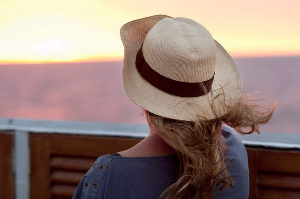 Stock Photo: 1889R-70840 a young woman wearing a hat and watching the sunset, galapagos equador