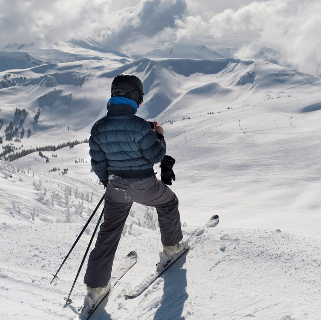 a skier pauses on the trail to look out over the mountains, whistler british columbia canada : Stock Photo