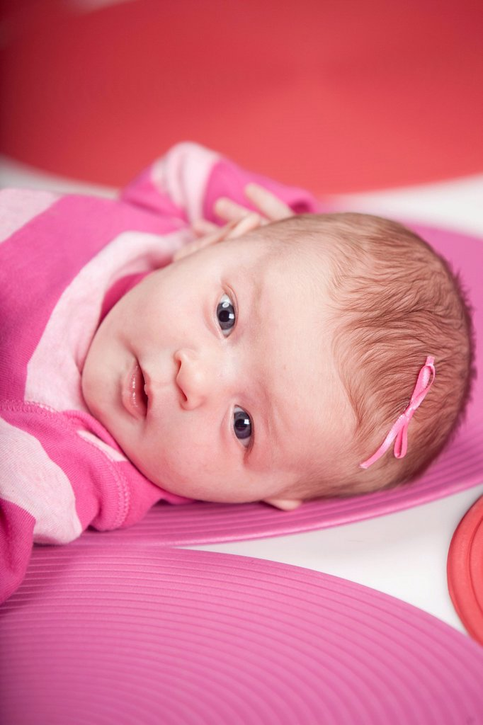 Stock Photo: 1889R-70971 a baby girl wearing pink and white and laying on red and pink polka dots, edmonton alberta canada