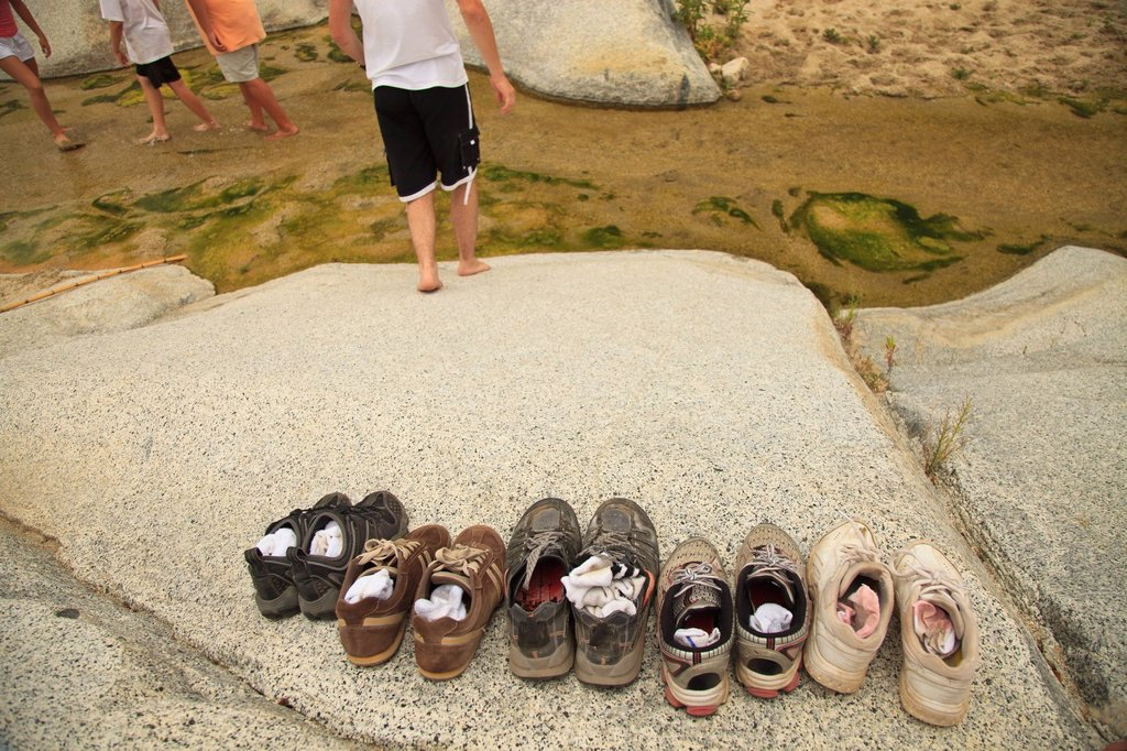 Stock Photo: 1889R-71099 a family leaves their shoes on the shore and walks in the shallow water at the sierra la laguna biosphere reserve, baja california sur mexico