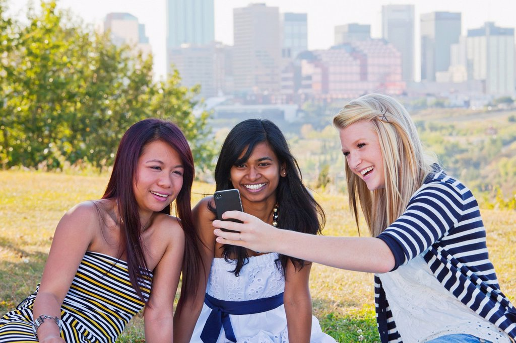 Stock Photo: 1889R-71333 friends looking at a smart phone with a city skyline in the background, edmonton alberta canada