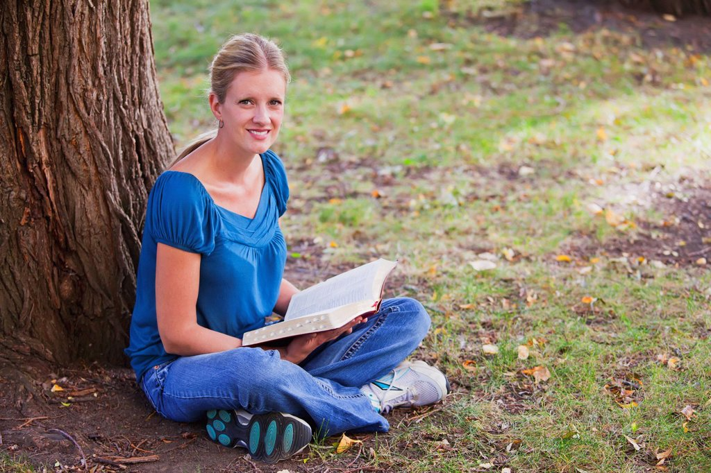 woman reading her bible in the park beside a tree, edmonton alberta canada : Stock Photo