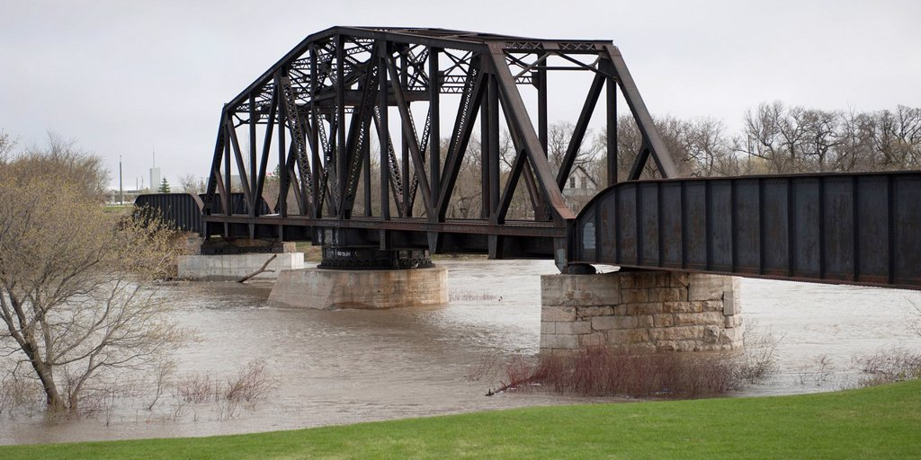 a bridge crossing assiniboine river with high waters after a flood, headingley, manitoba, canada : Stock Photo