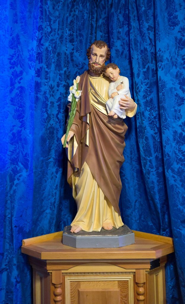 Stock Photo: 1889R-71897 statue of jesus holding a child in front of a blue curtain, northumberland england