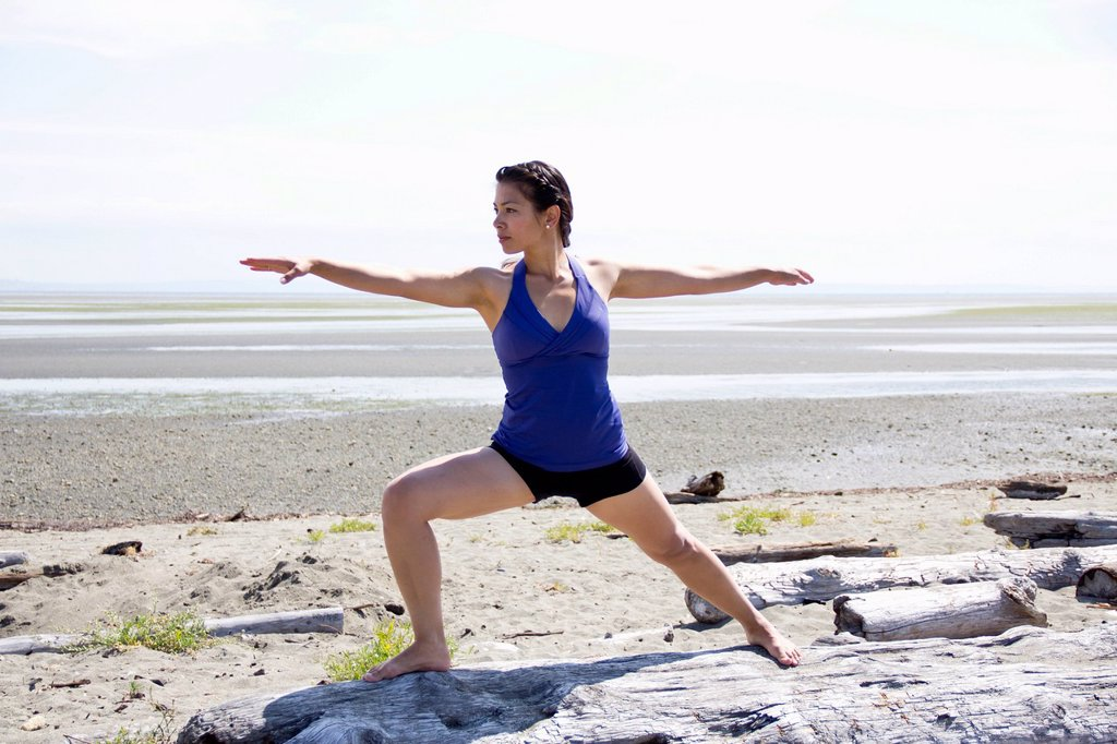 woman doing yoga on a beach, delta british columbia canada : Stock Photo