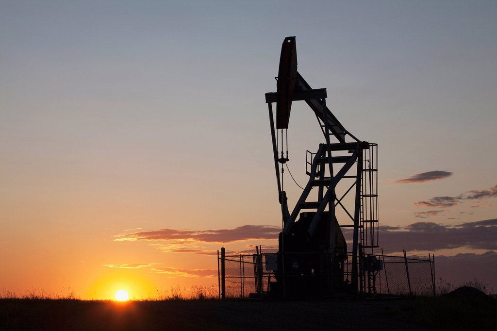 silhouette of pump jack with the orange glow of the sun rising on the horizon, longview alberta canada : Stock Photo