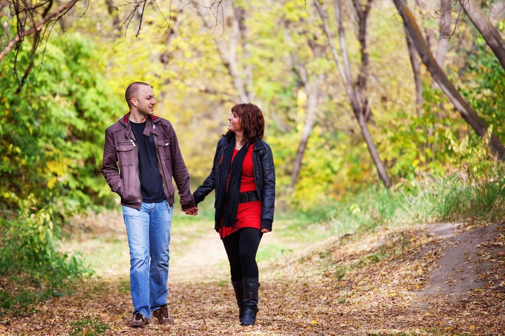 young married couple walking and talking together in a park in autumn, edmonton alberta canada : Stock Photo