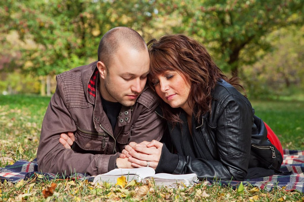 Stock Photo: 1889R-72297 couple reading bible and praying together in a park, edmonton alberta canada