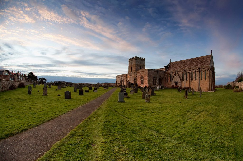 Path leading to a church building and cemetery, bamburgh northumberland england : Stock Photo