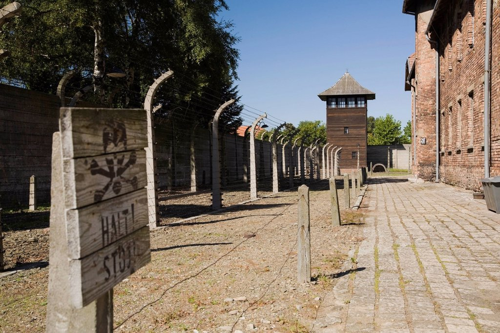 Stock Photo: 1889R-73486 Barb wire fences and guard tower in the auschwitz i former nazi concentration camp, auschwitz poland