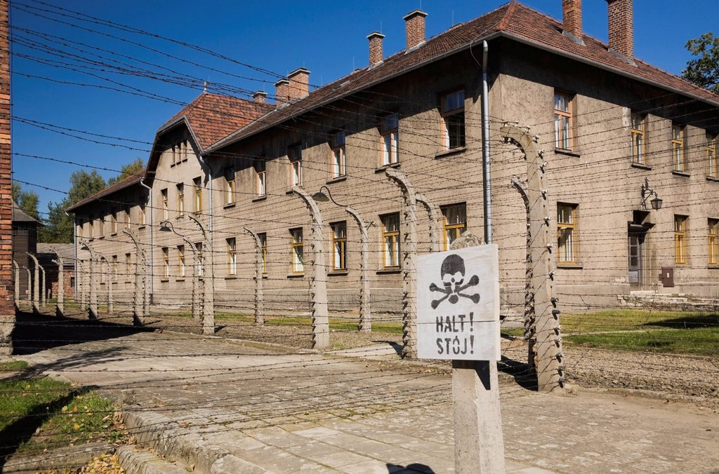 Stock Photo: 1889R-73487 Warning sign in front of a barb wire fence and building inside the auschwitz i former nazi concentration camp, auschwitz poland