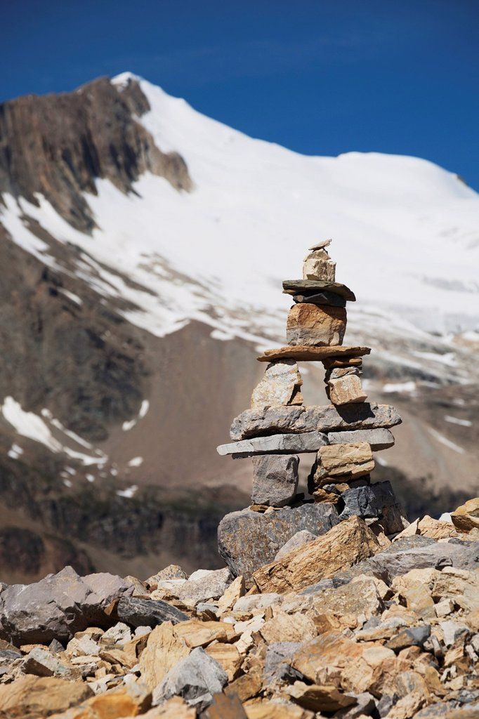 Stock Photo: 1889R-73864 Trail Marker Cairn On Rocky Ridge With Glacier Capped Mountain And Blue Sky, Field British Columbia Canada