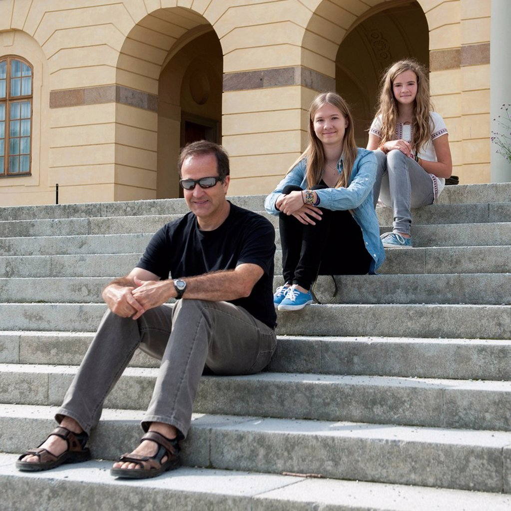 Stock Photo: 1889R-74024 A father and two daughters sitting on steps at drottningholm palace, stockholm sweden