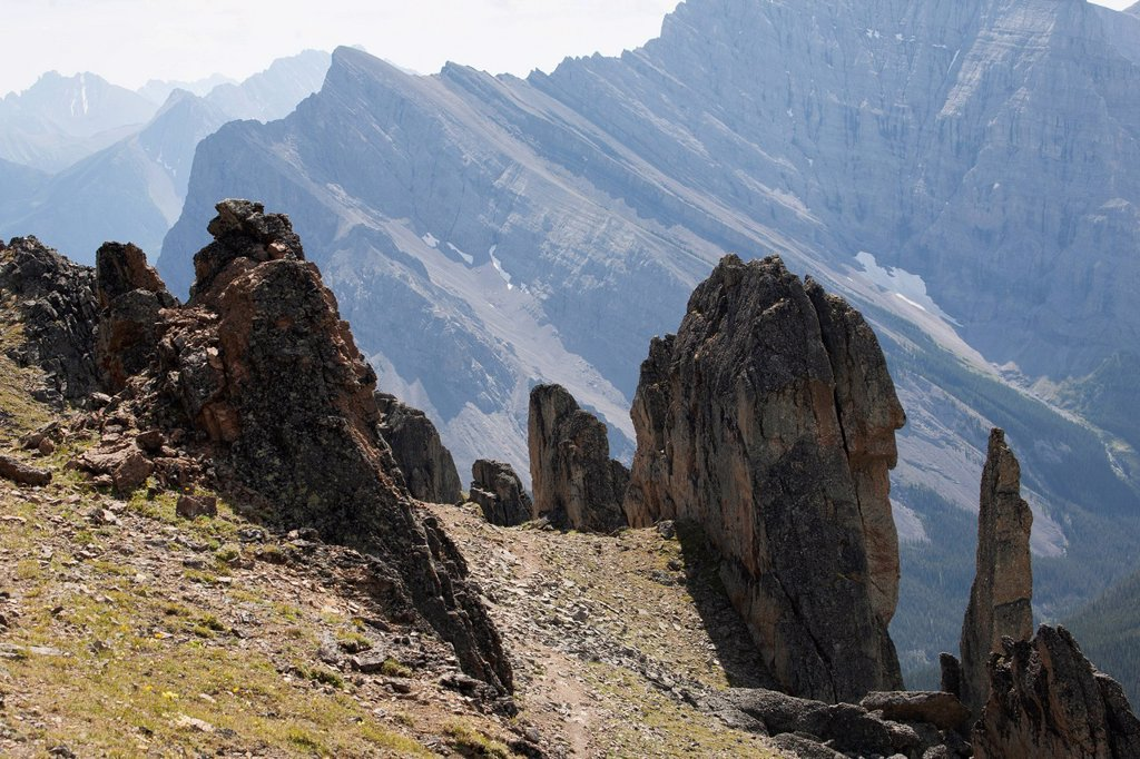 Large Rock Sentinels On Mountain Ridge With A Mountain Range In The Distance, Alberta Canada : Stock Photo