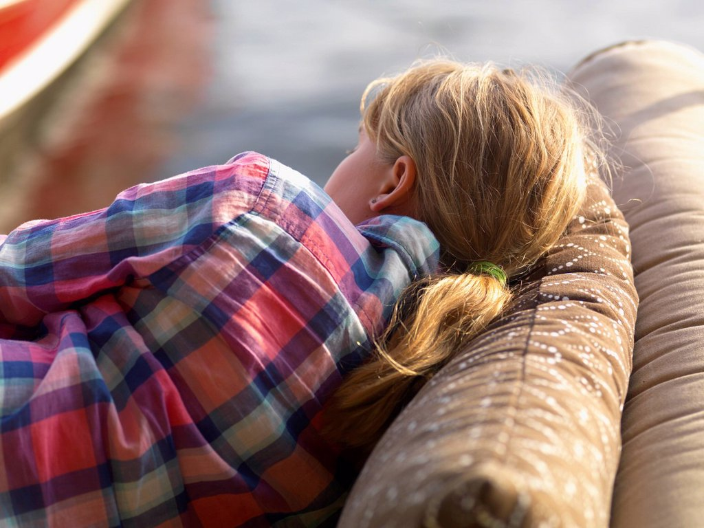 Stock Photo: 1889R-74396 A girl rests on a cushioned couch outdoors beside the water, lake of the woods ontario canada