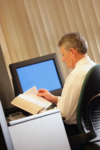 Stock Photo: 1889R-7455 Man reading book in his office
