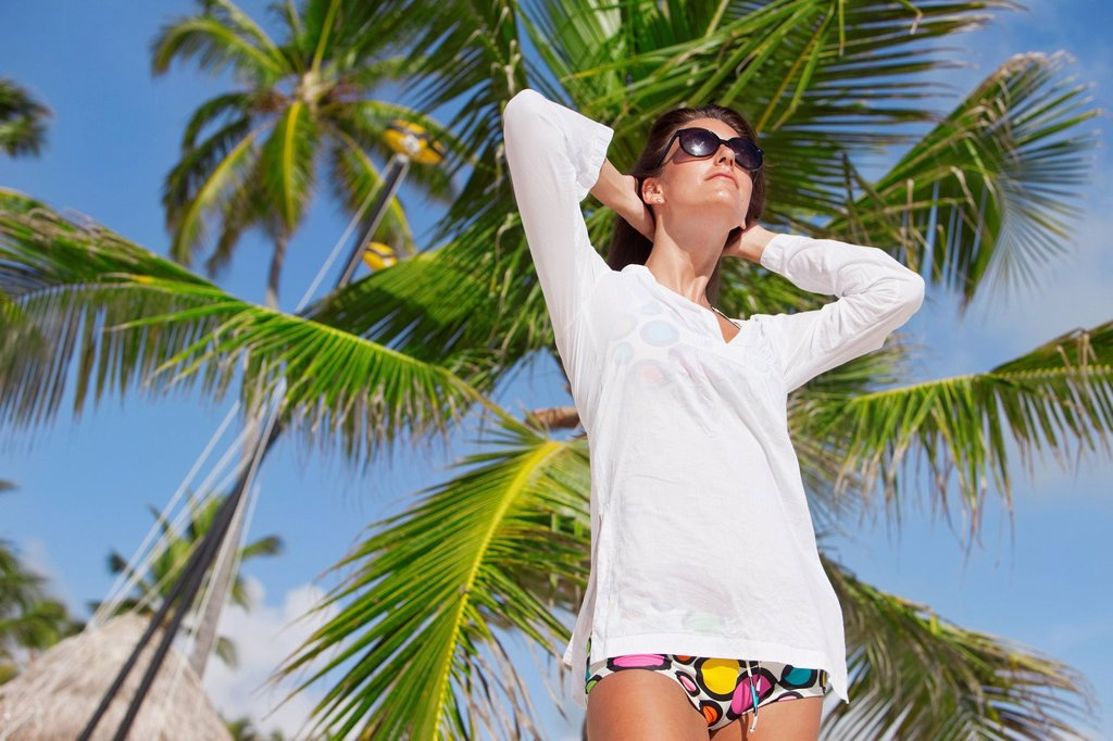 Portrait of a woman with a white swimsuit cover up and sunglasses with a palm tree in the background, punta cana la altagracia dominican republic : Stock Photo