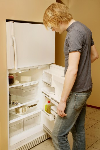 Looking in an empty fridge : Stock Photo
